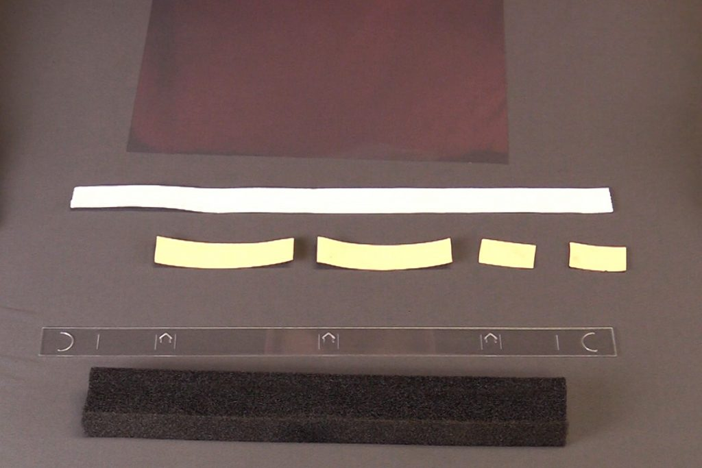 The components needed for a face shield, foam, elastic band, double sided tape, mylar sheet and laser cut  strip