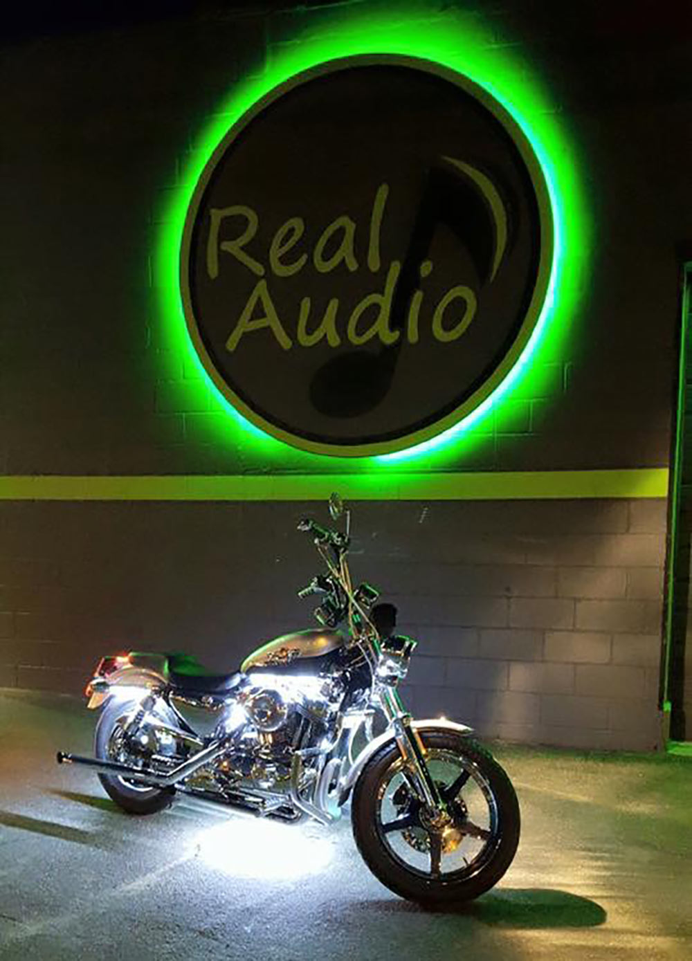 Photo of a custom motorcycle in front of Real Audio shop at night