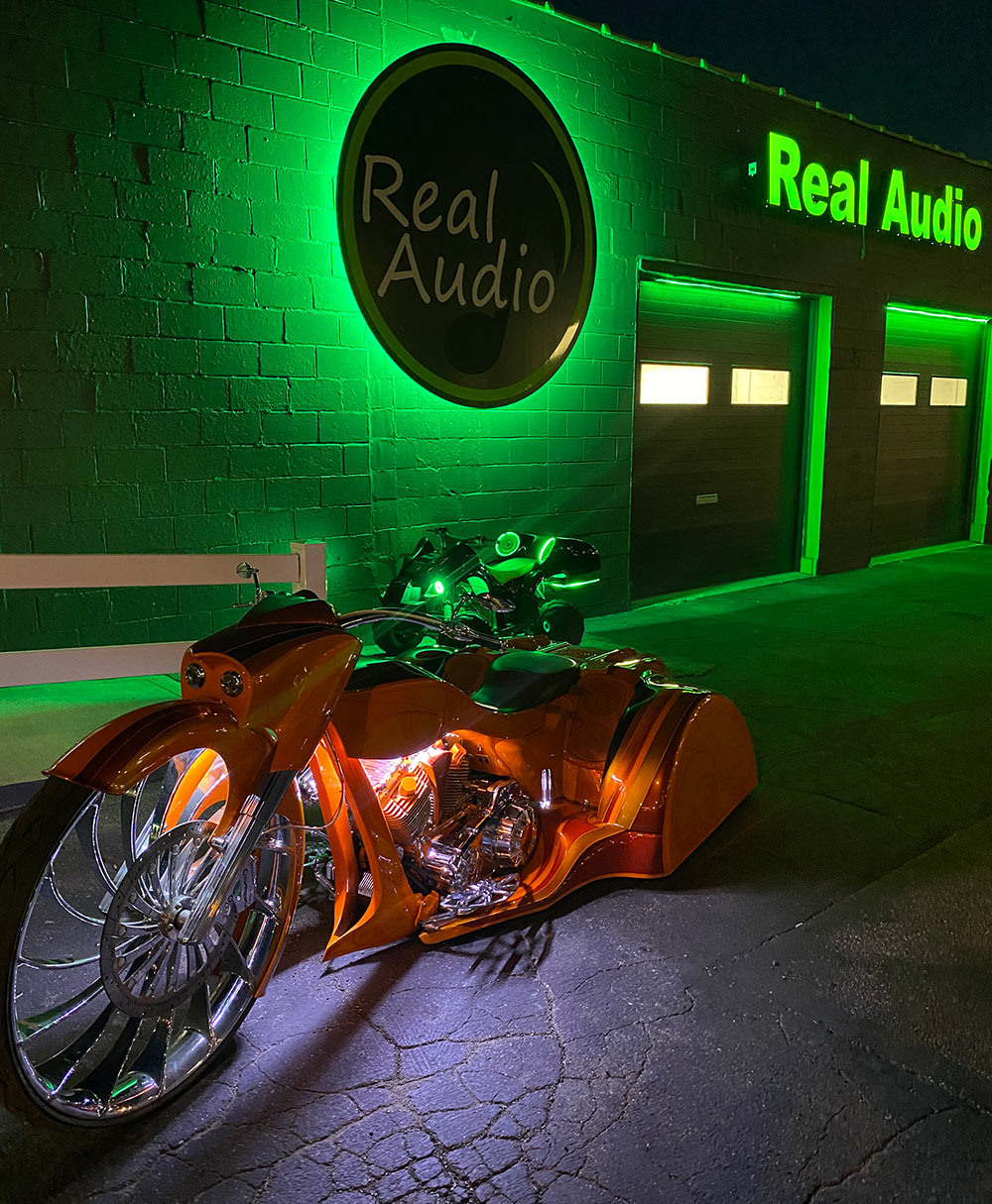 Photo of a custom trike in front of Real Audio shop at night