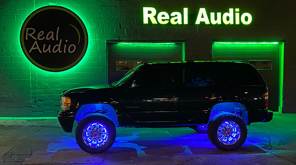 Photo of a lifted Tahoe in front of Real Audio shop at night